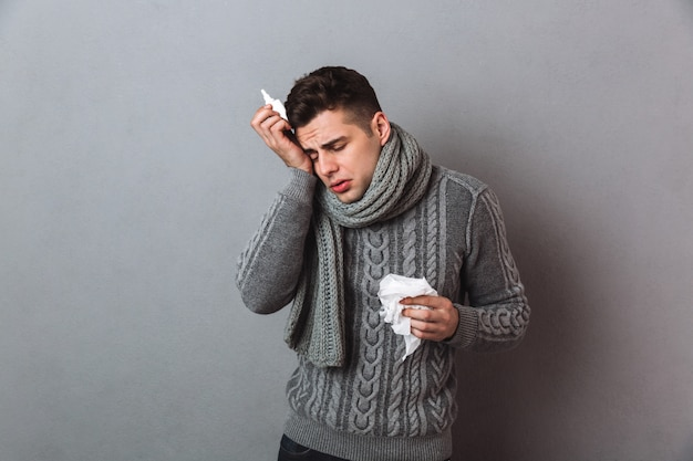 Sick man in sweater and scarf with serviette and spray having headache