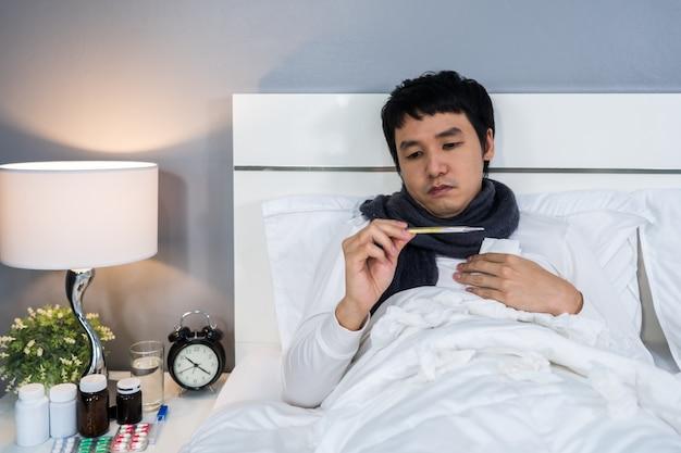Больной человек с помощью термометра для проверки его температуры в постели