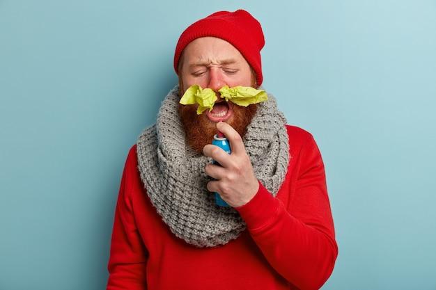 Uomo malato in vestiti caldi con fazzoletti di carta nel naso e spray per il mal di gola