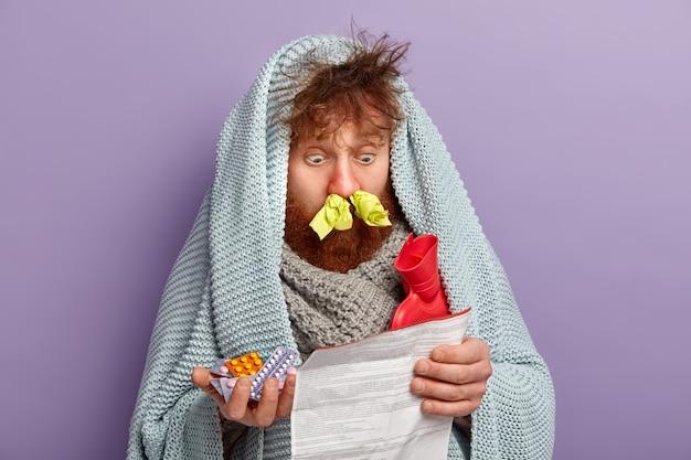 Uomo malato in vestiti caldi con pillole e sacca d'acqua