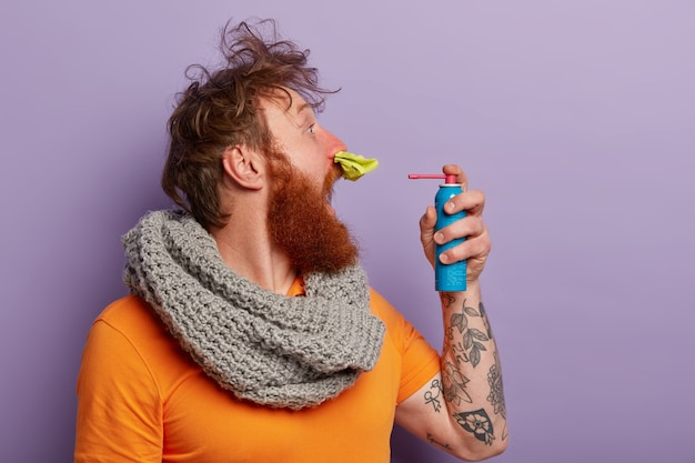 Uomo malato in vestiti caldi con spray per il naso
