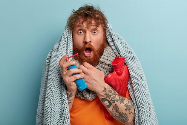 Uomo malato in vestiti caldi con spray per il mal di gola