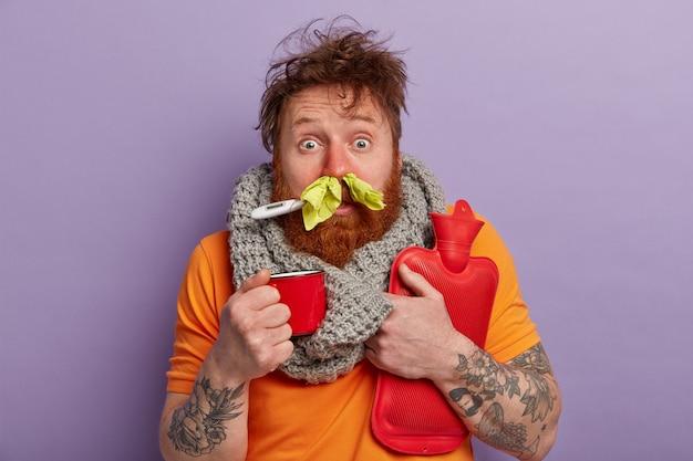 Uomo malato in vestiti caldi con termometro, tazza e sacca d'acqua