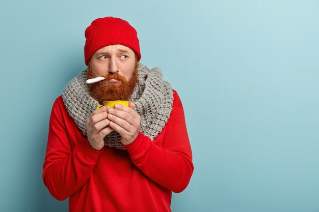 Uomo malato in vestiti caldi con termometro e tazza