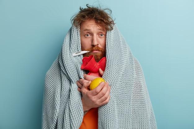 Uomo malato in vestiti caldi con termometro, tiene il limone, borsa dell'acqua calda
