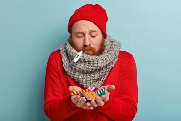 Uomo malato in vestiti caldi con termometro e pillole