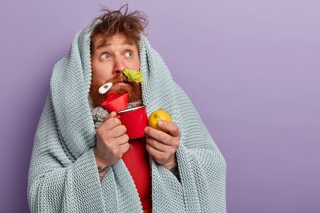 Uomo malato in vestiti caldi con termometro e sacca d'acqua