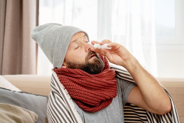 Sick man wearing grey hat and scarf