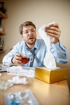 Больной человек во время работы в офисе, бизнесмен простудился, сезонный грипп. Бесплатные Фотографии