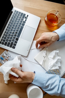 Sick man while working in office, businessman caught cold, seasonal flu.