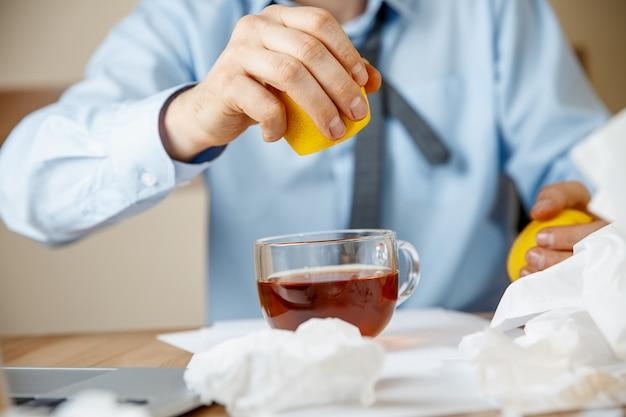 Uomo malato mentre lavorava in ufficio, uomo d'affari preso raffreddore, influenza stagionale.