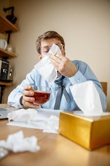 Sick man while working in office suffering seasonal flu.