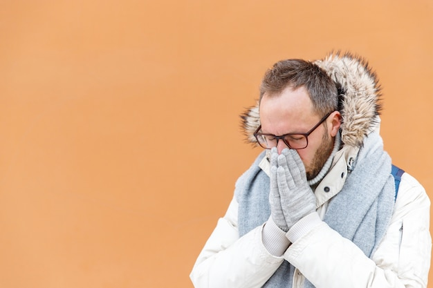 Sick man in white parka sneezing, suffering from stuffy nose, outdoors, orange wall on surface, copy space. common cold, flu season concept.