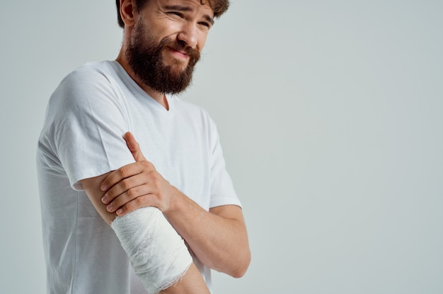 Sick man in a white tshirt with a bandaged hand posing hospital medicine
