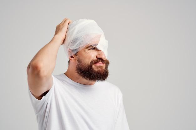 Sick man with bandaged head and eye hospitalization light background