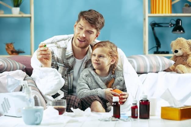 Больной мужчина с дочерью дома. домашнее лечение. борьба с болезнью. медицинское здравоохранение. семейная болезнь. зима, грипп, здоровье, боль, отцовство, концепция отношений. расслабление дома