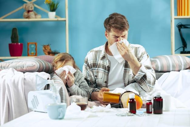 Больной мужчина с дочерью дома. домашнее лечение. борьба с болезнью. медицинское здравоохранение.