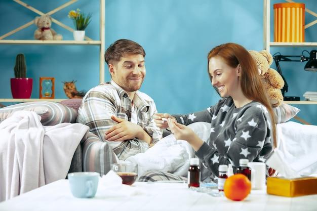 Uomo malato con febbre sdraiata a letto con la temperatura. la sua moglie si prende cura di lui. la malattia, l'influenza, il dolore, il concetto di famiglia. relax a casa. concetti sanitari.