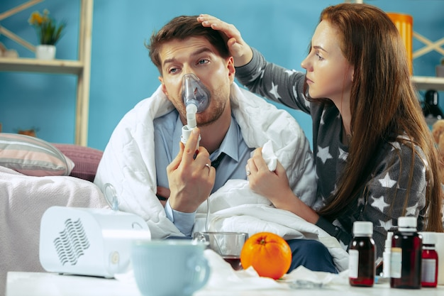 Sick man with fever lying in bed having temperature. the his wife take care for him. the illness, influenza, pain, family concept. relaxation at home. healthcare concepts.