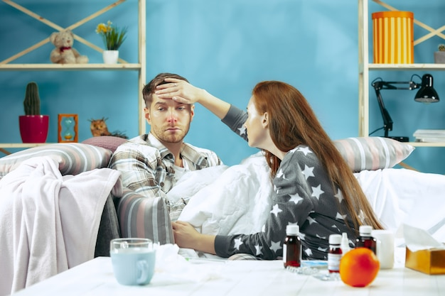 Uomo malato con febbre sdraiata a letto con la temperatura.
