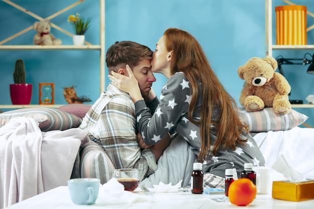 温度を持つベッドで横になっている発熱を伴う病人。彼の妻が彼の面倒を見る。病気、インフルエンザ、痛み、家族の概念。自宅でリラックス。ヘルスケアの概念。
