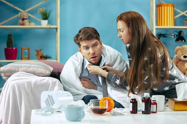 体温のあるベッドに横たわっている熱の病人。彼の妻は彼の世話をします。病気、インフルエンザ、痛み、家族の概念。自宅でのリラクゼーション。ヘルスケアの概念。