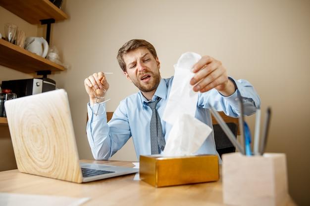 Uomo malato con il fazzoletto che starnutisce soffiando il naso mentre si lavora in ufficio, uomo d'affari preso freddo, influenza stagionale. influenza pandemica, prevenzione delle malattie, aria condizionata in ufficio causano la malattia