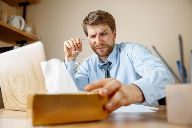 Uomo malato con il fazzoletto starnuti soffiando il naso mentre si lavora in ufficio, uomo d'affari preso raffreddore, influenza stagionale.