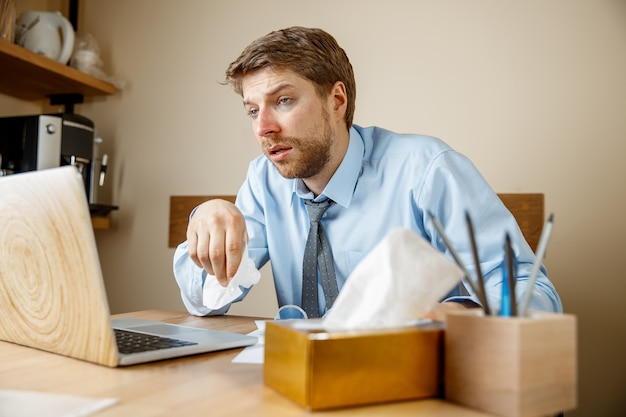 Sick man with handkerchief sneezing blowing nose while working in office, businessman caught cold, seasonal flu