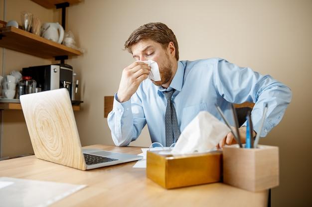 Uomo malato con il fazzoletto starnuti soffiando il naso mentre si lavora in ufficio