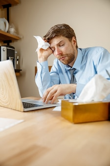 Sick man with handkerchief sneezing blowing nose while working in office