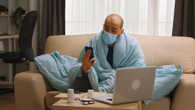 코비드-19 동안 체온이 높은 아픈 남자가 의사와 화상 통화를 하는 동안 마스크를 쓰고 있습니다.