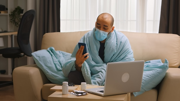 Sick man with high body temperature during covid-19 wearing a mask during a video call with his doctor.