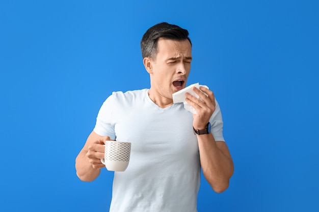 Sick man with hot tea on color surface