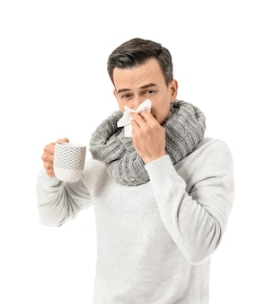 Sick man with hot tea on white surface