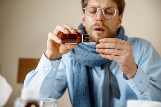 Uomo malato con miscela medicinale che lavora in ufficio