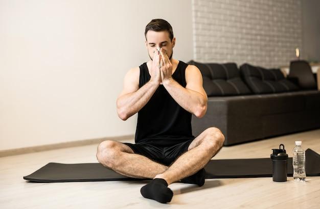 黒いヨガマットの上に座っている鼻水を持つ病人。家にいるコンセプト。ブルネットの若い男は、トレーニング後に鼻をかむ。気分が悪くなった場合は、自宅でスポーツを練習してください。