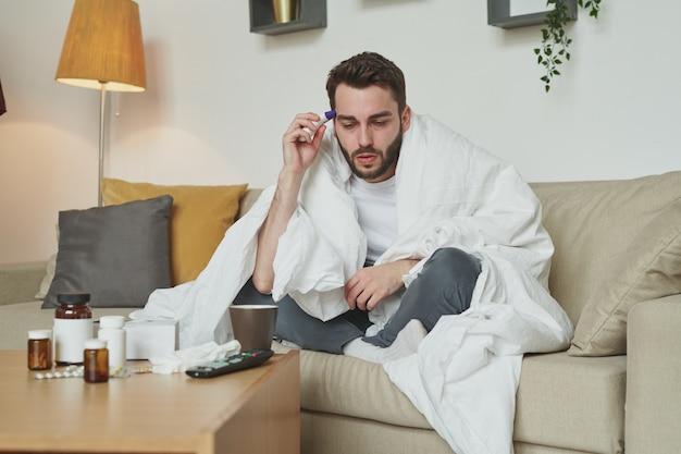 아픈 남자는 covid19로 인해 자기 격리 중에 가정 환경에서 소파에 앉아있는 동안 온도를 측정하는 따뜻한 담요에 싸여 있습니다.