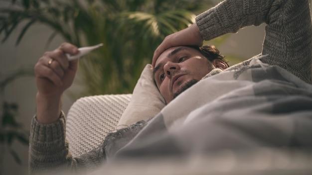 Больные лежат на диване и кладут руку на голову, держат термометр.