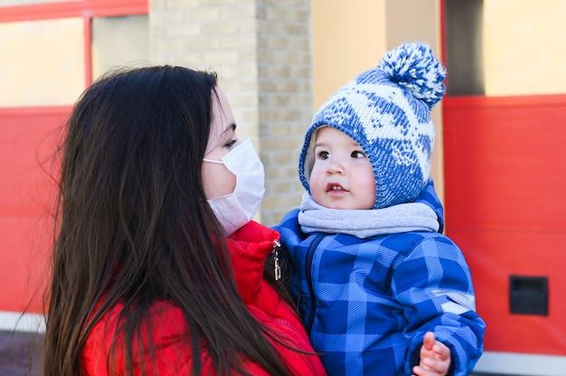 아픈 엄마가 아기와 함께 걷고 있습니다. 전염병 상황. 새로운 코로나 바이러스 (covid 19).