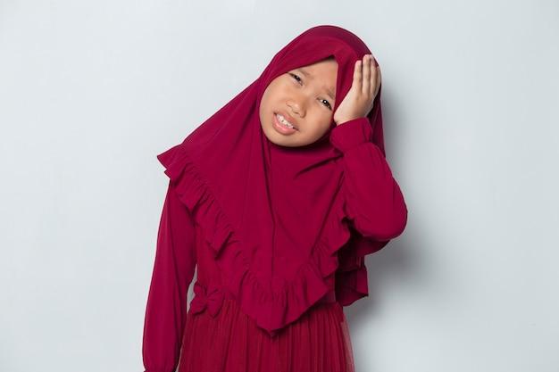 頭痛と問題を抱えた病気のイスラム教徒のアジアの少女