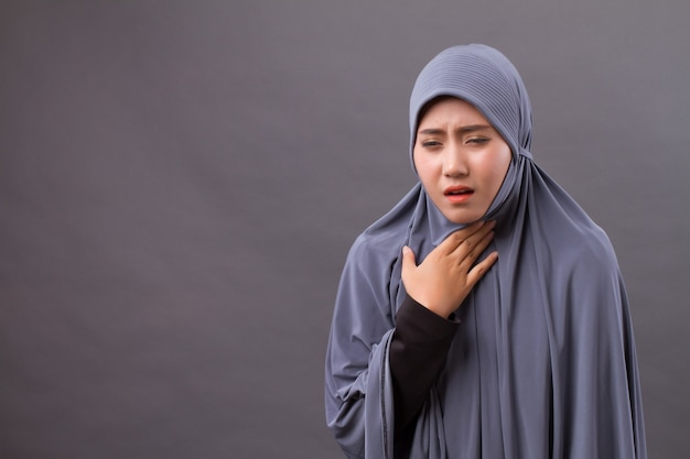 Sick muslim woman coughing with cold or sore throat