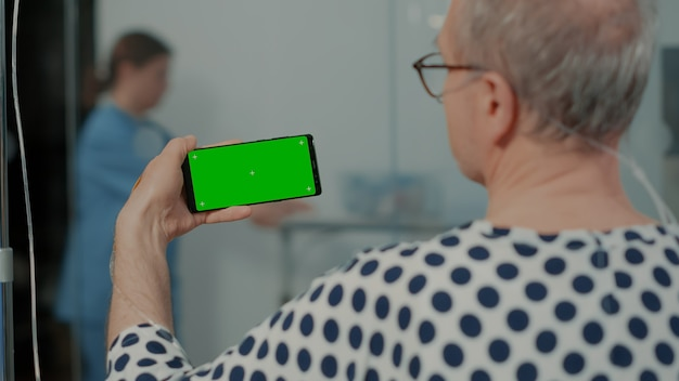 병원 병동에 있는 시설에서 치료 노인 환자를 위해 녹색 스크린 장치를 들고 있는 아픈 노인...