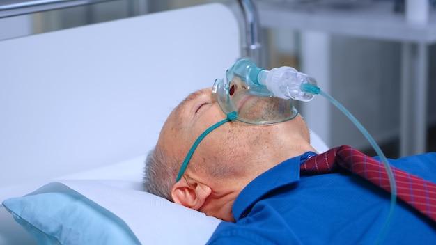 コロナウイルスcovid-19ヘルスケアの世界的な危機の間に病院のベッドに横たわっている呼吸マスクの病気の老人。現代の診療所の医療システムで呼吸器感染症に対して呼吸するための助けを得る
