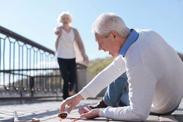 위대한 여자가 그에게 그녀의 길을 흔드는 동안 그의 약을 떨어 뜨리는 그의 길에 떨어지는 아픈 노인 슬픈 남자