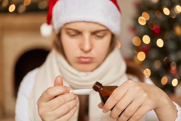 새해에 아프다! 산타 모자와 손에 약을 들고 앉아있는 흰색 스카프에 슬픈 아픈 여자는 기침 시럽을 마시고 숟가락에 붓는 것이 필요합니다.