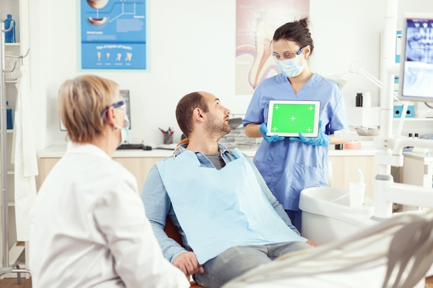 Sick patient looking at touchscreen gadget while speaking with stomatology senior doctor