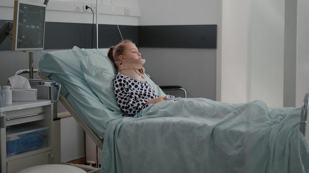 健康に害を及ぼす首の頸部カラーを身に着けているベッドで休んでいる病気の患者