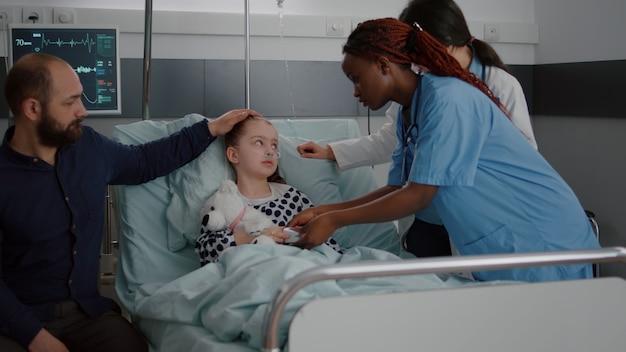 산소 비관을 착용하고 침대에서 쉬고 있는 아픈 환자가 소아과 의사와 이야기하는 동안...