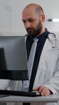 침대에 앉아 있는 아픈 환자가 종양 전문의와 회복 치료에 대해 이야기하고 있습니다. 병원 병동의 컴퓨터 모니터링 증상에 대한 개업 의사 타이핑 테스트 결과